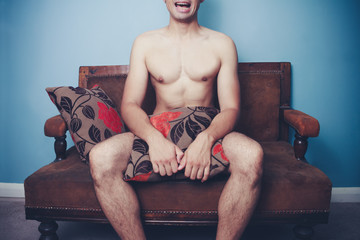 Young naked man on sofa with disturbed look on his face