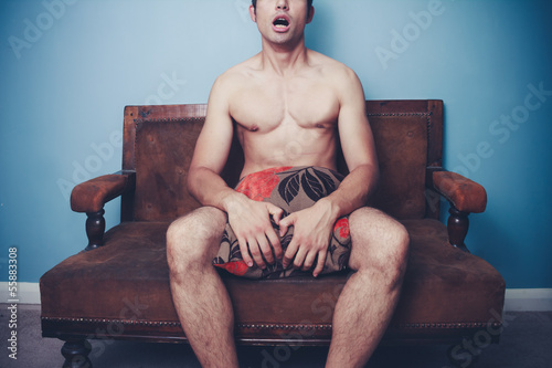 Young naked man on sofa is startled