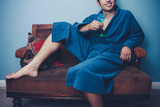 Happy young man in dressing gown drinking cocktails