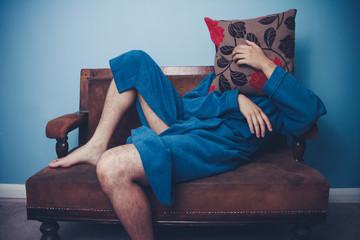 Man in dressing gown hiding behind cushion