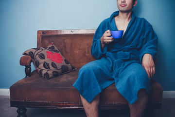 Young man drinking from cup on vintage sofa