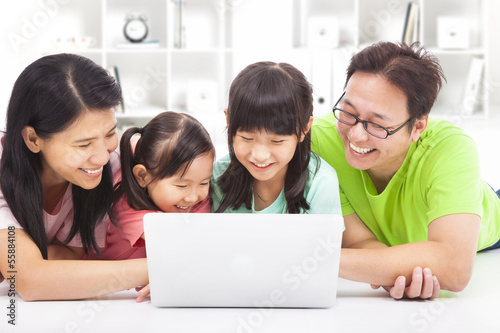 happy family with children looking at laptop