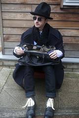 strange man wearing black coat hat hold suitcase