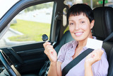 senior smiling woman holding car key and empty white card