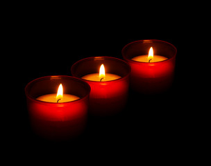 Red votive candles burning in the dark, black background