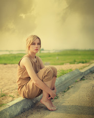 beautiful girl sitting on the edge of the road