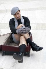pensive man in check cap sitting in broken trunk