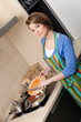 Beautiful woman in striped apron slices vegetables