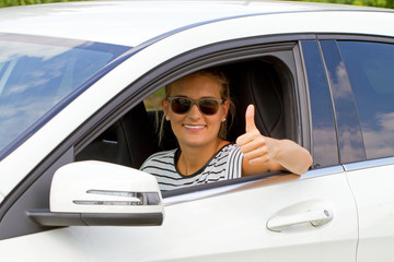 Junge Autofahrerin mit Daumen nach oben