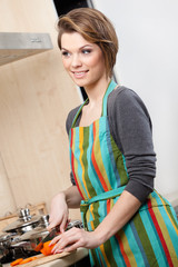 Pretty woman in striped apron cooks vegetables