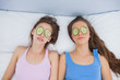 Friends relaxing in bed with cucumber on eyes