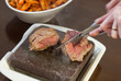 Steak sizzling on hot stone plate being sliced
