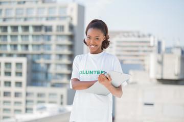 Smiling volunteer woman holding clipboard