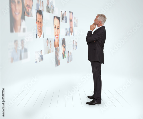 Thoughtful businessman looking at a wall covered by profile pict