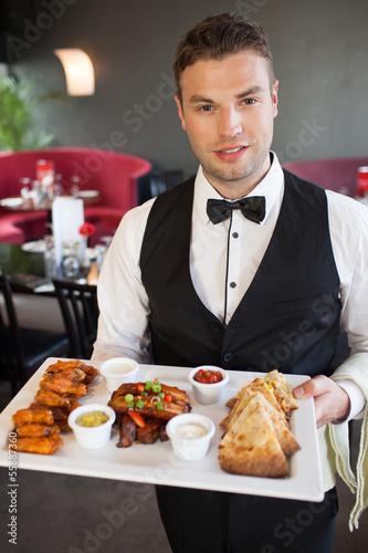 Handsome waiter serving appetizing finger food platter
