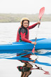 Happy woman rowing on lake