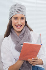 Smiling pretty brunette with winter hat on writing on notebook