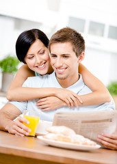 Woman embraces eating boyfriend who sits at the kitchen