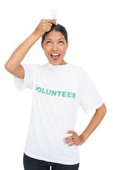 Happy model wearing volunteer tshirt holding light bulb above he