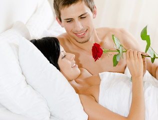 Man lying in bed-room gives scarlet rose to woman