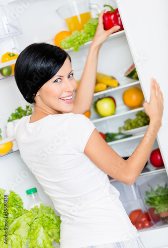 Woman takes bell pepper from the refrigerator full of vegetables