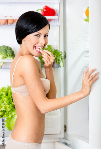 Young woman eating near the opened fridge