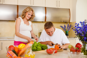 Pregnant woman and her husband prepare vegetable salad at home