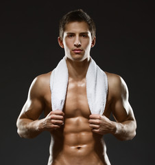 Half-length portrait of naked sportsman with towel