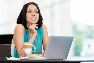 Girl wearing blue dress works at the laptop