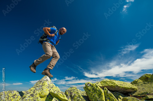 Hiker jumps over stones in mountains