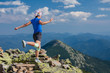 Woman athlete is jumping over stones in mountains