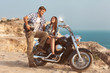 Stylish couple on a motorcycle. He put his foot on the exhaust p
