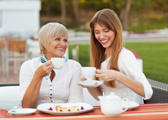 adult mother and daughter drinking tea or coffee and talking out