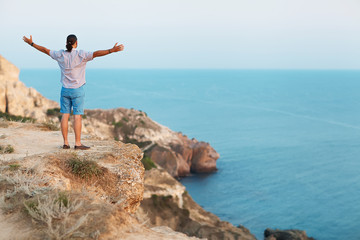 Man standing on a rock by the sea . Concept of freedom.