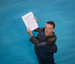 Senior man holding mortgage loan document in water