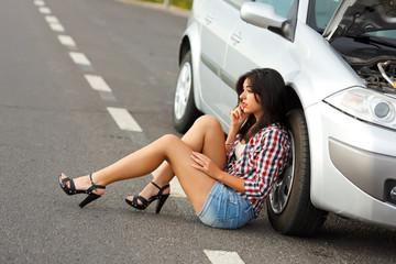 Woman sitting on ground near broken car