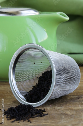 granulated black tea in a metal cup on a wooden table
