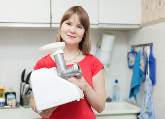 Woman with electric mincing machine