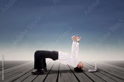 Businessman doing bridge yoga outdoor