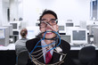 Close-up angry businessman tied in rope and cable at office