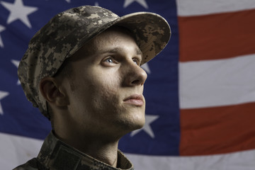 Young soldier in front of flag, horizontal
