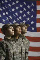 Three young military personnel in front of flag, vertical