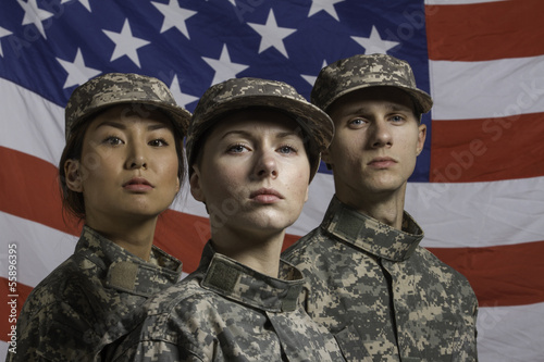 Three military personnel in front of flag, horizontal