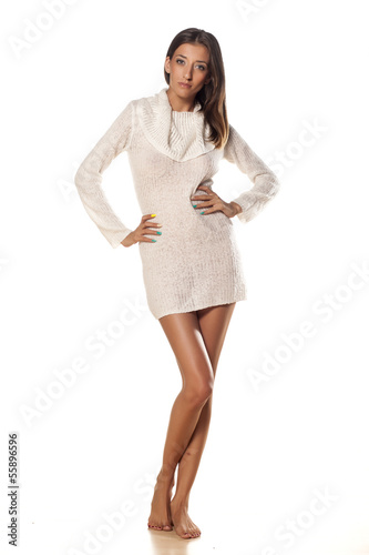 serious skinny girl in white sweater posing on white