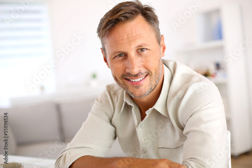 Poster Attractive smiling man relaxing at home