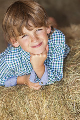 Young Happy Boy Smiling on Hay Bales