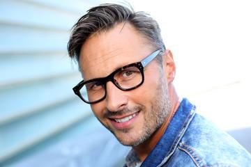 Smiling man wearing eyeglasses and blue jeans jacket