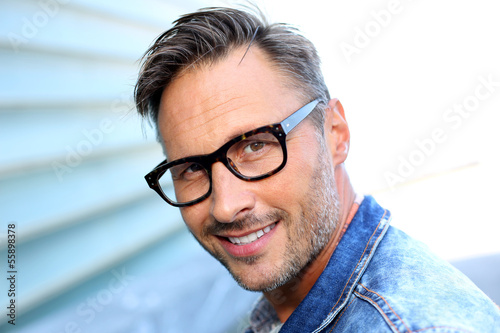 Smiling man wearing eyeglasses and blue jeans jacket