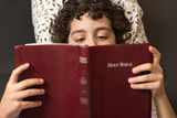 Child reading and studing the Holy Bible at home