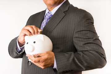 Businessman holding a piggybank and saving change